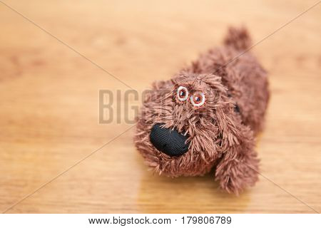 Little soft toy dog on a wooden table, blurry