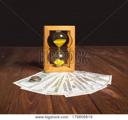 glossy old-style hourglass standing on american dollar bills and coins