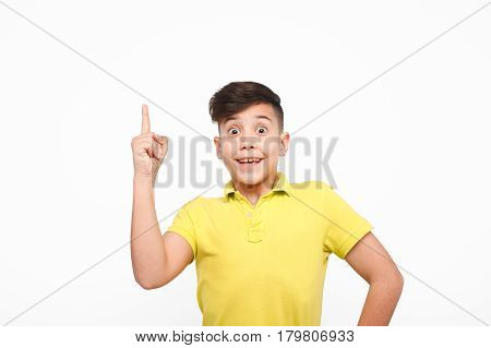 Little iby in yellow t-shirt holding finger up gesturing idea on white background.
