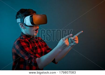 Shocked little boy pointing with the finger on a side in VR goggles.