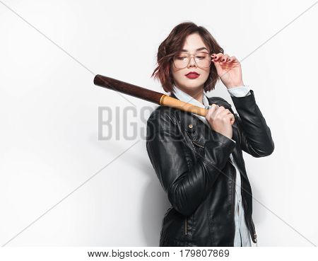 Young stylish girl wearing glasses and black leather coat and holding batt on white background.
