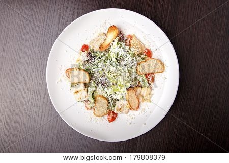 Traditional Caesar salad with chicken bacon lettuce letuk croutons onions tomatoes sprinkled with parmesan cheese.