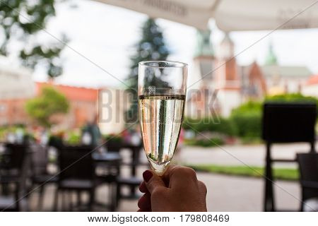 A woman is holding a glass of champagne in a cafe on the background of the Wawel Castle in Krakow, Poland.