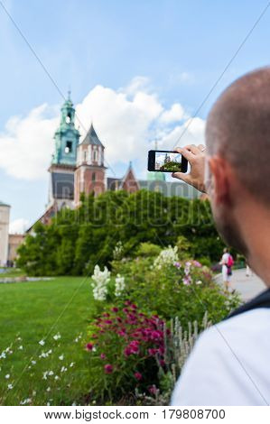 A male traveler takes pictures on his mobile phone against the background of the Wawel Castle, Cracow, Poland.