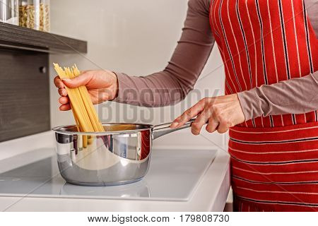 Close up of hands of woman putting pasta into pot. She is standing in kitchen