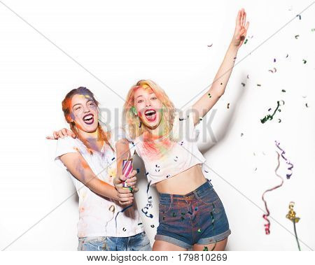 Two cheerful women covered with Holi colors with the party popper. Horizontal studio shot.