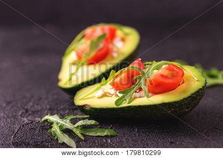 Avocado Stuffed With Feta Cheese, Arugula And Tomatoes
