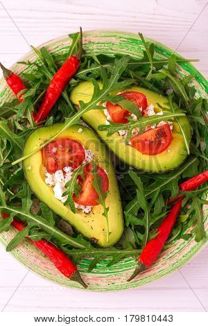 Avocado Stuffed With Feta Cheese, Arugula And Tomatoes