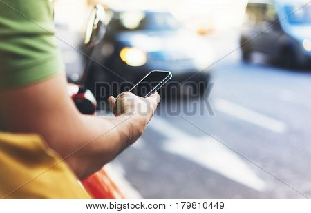 Man pointing on screen smartphone on background cars tourist hipster waiting using in hands mobile phone traveler connect wifi internet and calls taxi headlights auto on backdrop city street mockup
