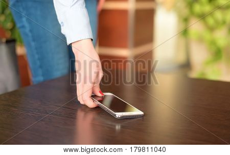 Woman Hand Pick Up The Phone From The Table