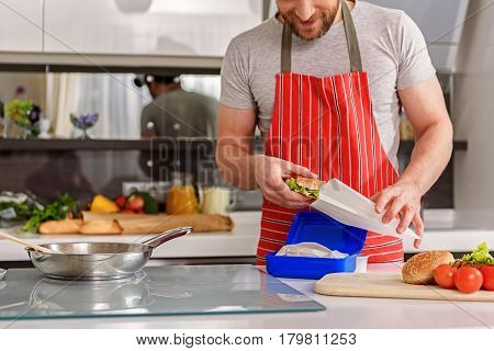 Joyful man is packing breakfast into package. He is standing in kitchen and wearing apron