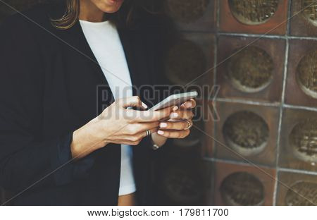 Women using smartphone isolated hipster manager holding mobile gadget girl texting message sms connect concept blur background brick mockup female hands touch digital screen user social network