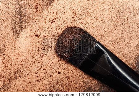 Black Make-up Artist's beauty Brush on golden Painted Background