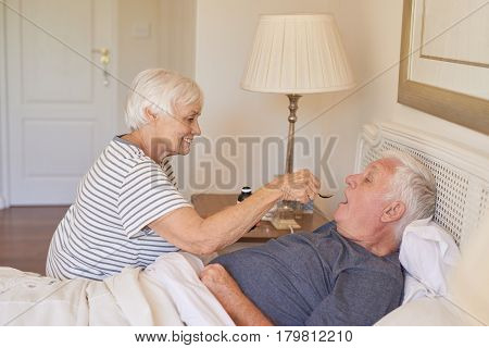 Sick senior man being given medicine by his caring and devoted wife while lying in bed at home in the morning