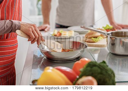 Close up of woman hands mixing ingredients in frying pan by wooden tool. Man is standing near table on background