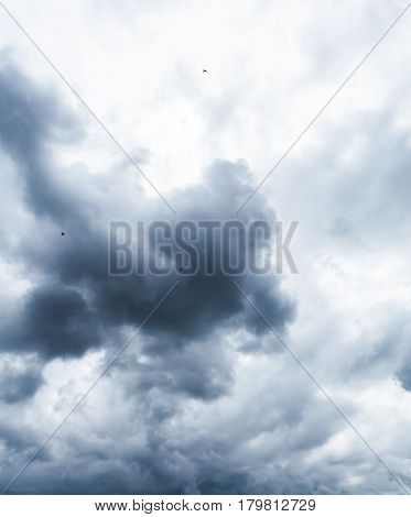 Background of dark clouds. A dramatic autumn sky with gray dense clouds before downpour.