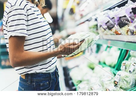 Young woman shopping healthy food in supermarket blur background. Female hands buy products cabagge using smartphone in store. Hipster at grocery using smartphone. Person comparing price of produce