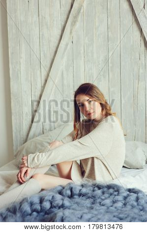 young woman in knitted cardigan and warm socks wake up in the morning in cozy scandinavian bedroom and sitting on bed with white bedlinen. Casual lifestyle in modern interior