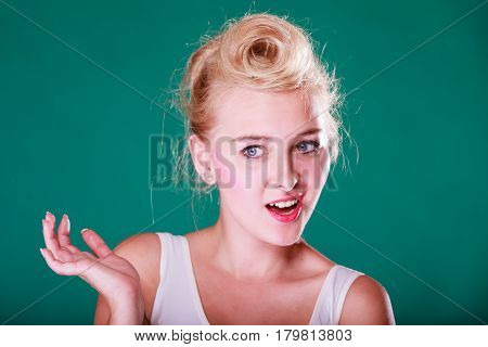Face expression emotions concept. Young woman with pin up hair being astonishment shocked and disgust. Studio shot on green background