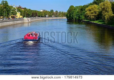 Pleasure boat on the river. Summer day. Sunny weather. The beautiful landscape of the Park and the river in the city. A day off in the city. Elagin island. Saint-Petersburg. Russia.