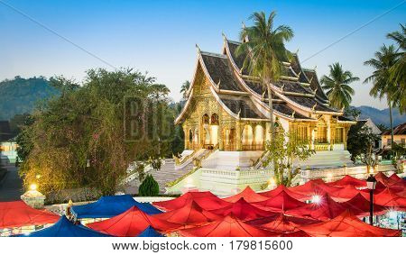 Wat Xieng Thong temple and night market at blue hour in Luang Prabang - Laos PDR world famous tourism destination - Travel concept with antique landmark in south east Asia exclusive city destinations