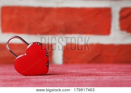 Heart shaped padlock on brick wall background