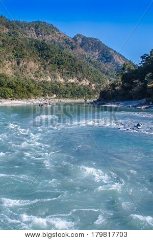 View of River Ganga and amazing blue sky at beautiful colorful day with a colorful jungles on a background houses. Rishikesh. India.