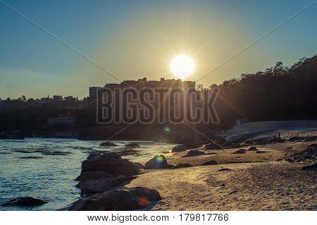 Amazing sunset on the Ganga river bank with a big stones on the beach near Rishikesh Uttarakhand India