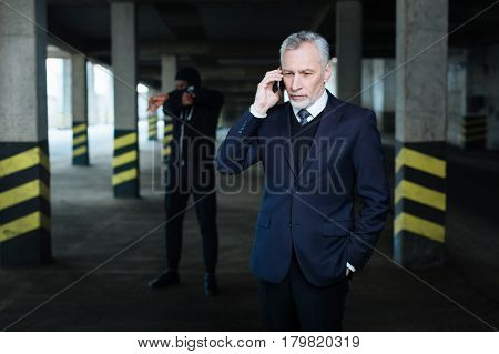 Call to relatives. Anxious serious handsome businessman holding a cell phone and making a call while being at gunpoint