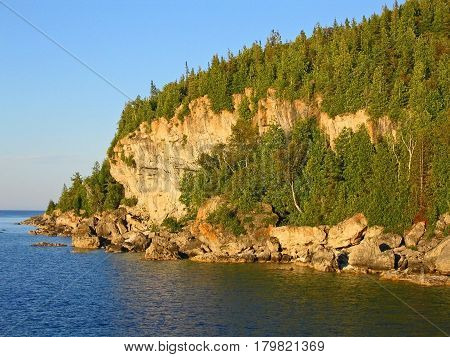 The waters of Georgian Bay meet the rocky tree-lined shore of Bruce Peninsula in the late light of day. This northern outcropping of rock is part of the Niagara Escarpment. At its southern end is Niagara Falls. Ontario, Canada.