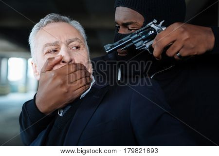 Do not say a word. Dangerous calm strong criminal holding a gun and threatening a businessman while covering his mouth with his hand