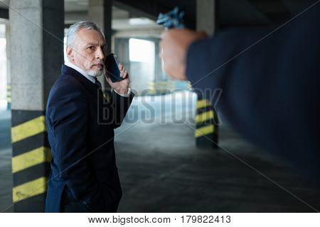 Being in danger. Unhappy worried pleasant man looking at the handgun and making a call while being at gunpoint