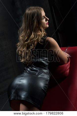 Girl in a leather dress on a red armchair