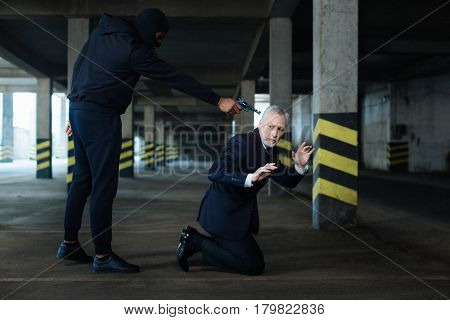 Stand on the knees. Serious scared unhappy businessman standing on his knees and raising his hands up while being at gunpoint