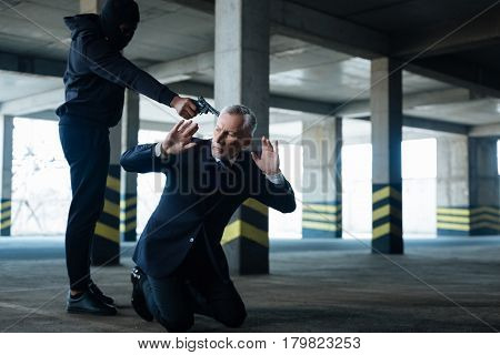 I want money. Aggressive dangerous male criminal wearing a mask and threatening a businessman while abducting him