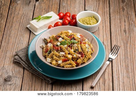 pasta  with pesto feta cheese and cherry tomatoes
