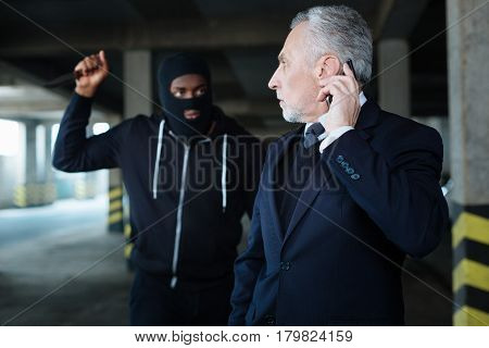 Being scared. Sad frightened elderly man looking at his abductor and calling his relatives while being kidnapped