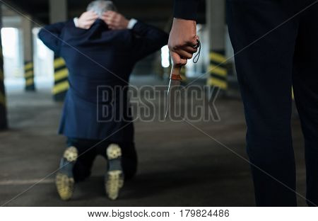 Cold steel. Selective focus of a knife being in hands of a ruthless hardened criminal while kidnapping the businessman
