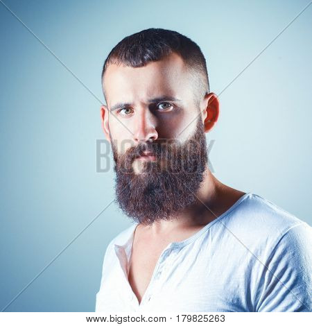 Portrait of handsome bearded man standing, isolated on grey background