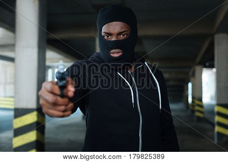 Hiding the face. Aggressive dangerous afro American man wearing a mask and holding the gun while hiding his face