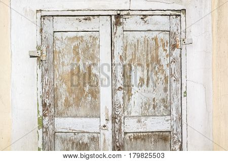 Closeup obsolete damaged wooden door painted white background