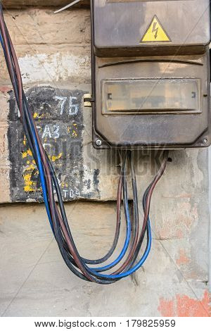 Close up of obsolete electrical board on wall with colorful cords
