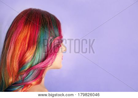Trendy hairstyle concept. Young woman with colorful dyed hair on color background poster