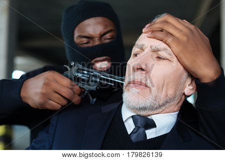Give me money. Aggressive dangerous male criminal wearing the mask and hiding his face while threatening a businessman with a gun