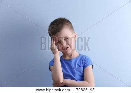 Little boy suffering from headache on color background