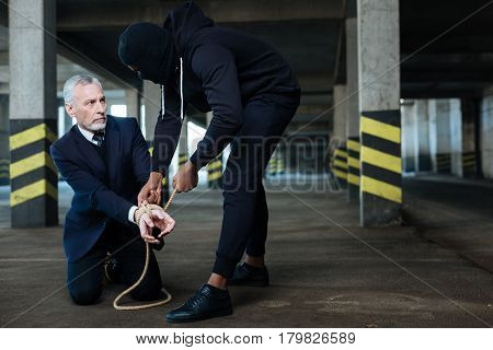 What will you do to me. Serious unhappy stressed businessman sitting on his knees and having his hands tied while being held hostage