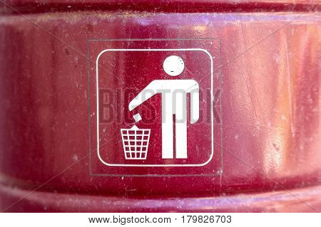 Closeup red metal dustbin with white sign on