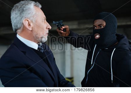 Where are your money. Aggressive greedy well built robber holding a handgun and pointing with it at the businessman while asking his about his money