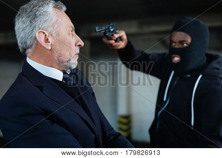 Dangerous situation. Serious shocked unhappy man standing near the criminal and looking at him while being at gunpoint