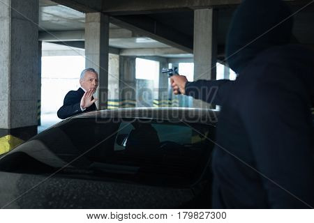 I will give you everything. Nice pleasant elderly man standing near his car and looking at the gun muzzle while trying to speak with the criminal